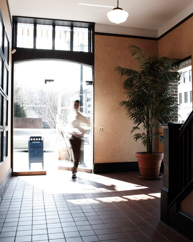Photograph of employee opening glass door into lobby